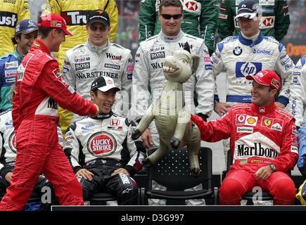 (dpa) -Ferrari's German Formula One world champion Michael Schumacher (L) arrives late as Formula One drivers pose - Stock Photo