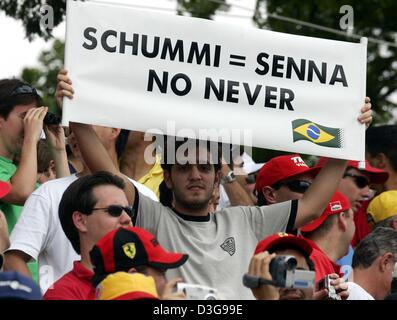 (dpa) - A Brazilian Formula One fan holds a banner with the inscription 'Schummi = Senna no never' in his hands - Stock Photo