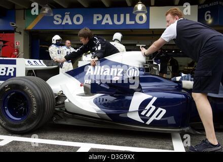 (dpa) - BMW-Williams Formula One mechanics push a racing car through the pits at the Interlagos race track in Sao - Stock Photo