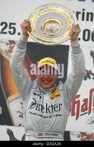 (dpa) - British Mercedes pilot Gary Paffett cheers as he lifts the trophy during the award ceremony in Nuremberg, - Stock Photo