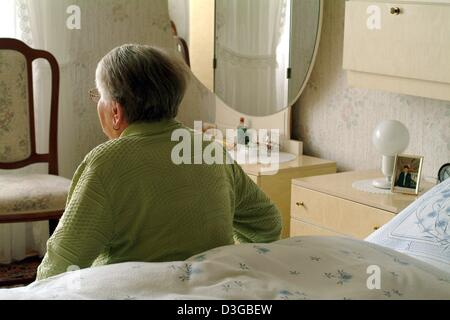 (dpa) - An older woman sits on the bed in her bedroom in Frankfurt, Germany, 19 October 2004. - Stock Photo