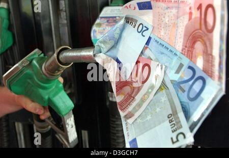 (dpa files) - A filler plug 'sucks in' euro notes in a staged photo at a filling station in Frankfurt Oder, eastern - Stock Photo