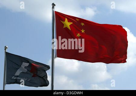 (dpa) - The Chinese national flag and a F1 flag flutter in the wind at the new formula one racing circuit in Shanghai, - Stock Photo