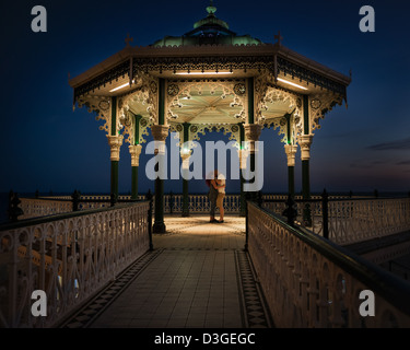 Lovers embrace in the light of a bandstand on Bright seafront - Stock Photo