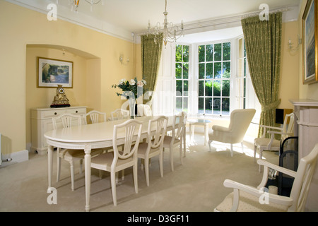 White painted dining room furniture in a traditionally proportioned room. - Stock Photo