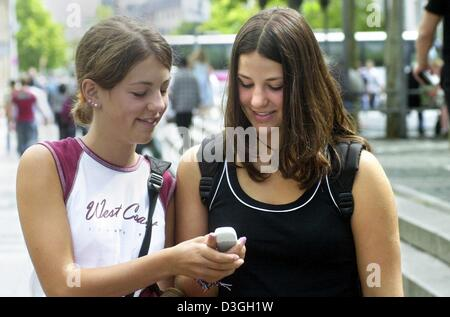 (dpa) - Roxanne (L) and her friend Anahita send text messages with their mobile phone in Frankfurt Main, Germany, - Stock Photo