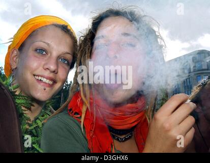 (dpa) - Two young woman sit next to each other and smoke a joint during the Hemp Parade in Berlin, 14 August 2004. - Stock Photo