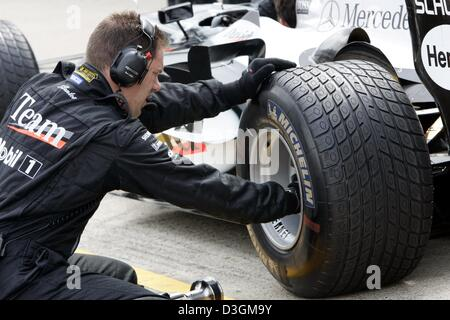 (dpa) - A McLaren-Mercedes mechanic screws a rain tyre onto the wheel rim of David Coulthard's race car at the Silverstone - Stock Photo