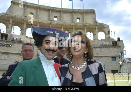 (dpa) - Italian actress Claudia Cardinale smiles as she poses with a mime imitating Charles Chaplin in front of - Stock Photo