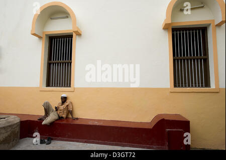 Man resting in front of a mosque, Old Town, Mombasa, Kenya - Stock Photo