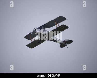 Vintage bi-plane flying over Quorn station just after dropping the commemorative poppies at great central railways - Stock Photo