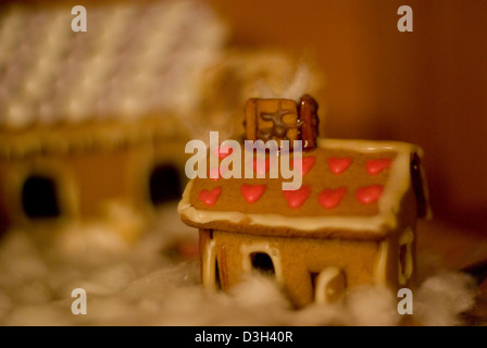 A gingerbread house with roof decorated with red hearts and snowy garden - Stock Photo