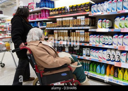 An elderly lady in a wheelchair and her carer or assistant look at hair products and shampoo in a supermarket. - Stock Photo