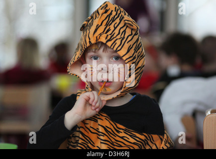 A German five year old boy dresses as a tiger eating a saltstick during a carnival party in the kindergarten. Leipzig, - Stock Photo