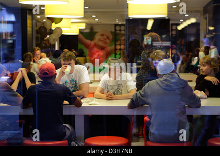 Stockholm, Sweden, young people sitting in a fast food restaurant - Stock Photo