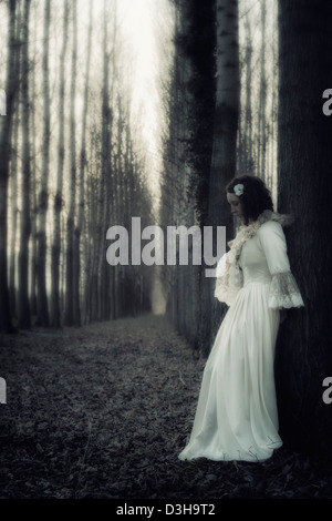 a woman in a dark forest - Stock Photo