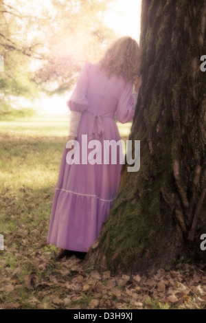 a woman in a pink dress is leaning against a trunk - Stock Photo