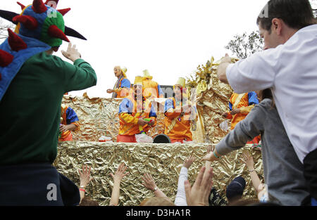 Feb. 10, 2013 - New Orleans, LOUISIANA, UNITED STATES - A masked float rider throws beads to the cheering crowd - Stock Photo
