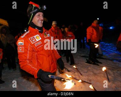 (dpa) - German formula one pilot and world champion Michael Schumacher holds a lighted torch in his hands as he - Stock Photo