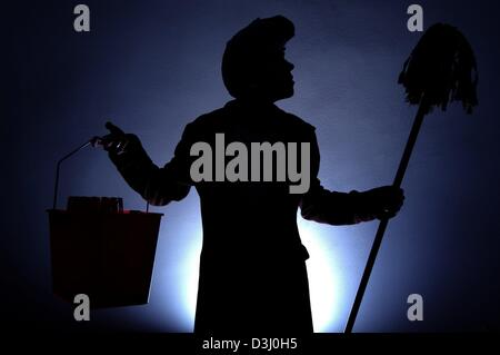 (dpa) - The symbolic photo shows the silhouette of a cleaning woman holding up a bucket and a mop, photographed - Stock Photo