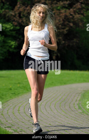 (dpa file) - The picture, dated 6 May 2005, shows a young woman jogging in Gescher, Germany. - Stock Photo