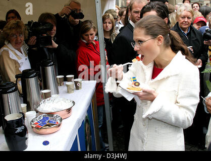 (dpa) - Swedish Crown Princess Victoria (R) tastes from a Swedish delicacy as she attends the festivities on the - Stock Photo