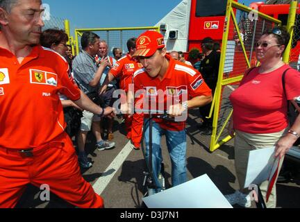 (dpa) - German Formula 1 champion Michael Schumacher (C) drives through the new pit lane at the city course on his - Stock Photo