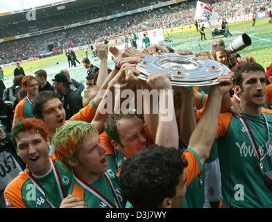 (dpa) - Bremen's soccer players cheer and jubilate as they carry the German Bundesliga trophy across the pitch after - Stock Photo