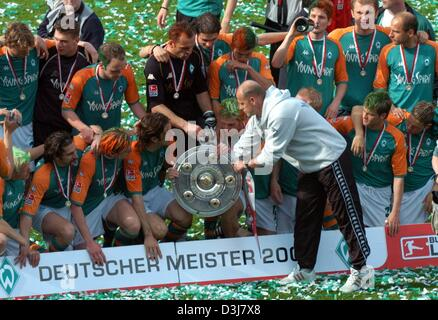 (dpa) - Bremen's soccer coach Thomas Schaaf hands the German Bundesliga trophy to his players for a group picture - Stock Photo