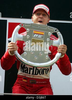 (dpa) - German formula one world champion Michael Schumacher of Ferrari holds up his trophy after his fifth straight - Stock Photo