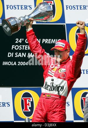 (dpa) - German formula one pilot and world champion Michael Schumacher (Ferrari) holds the trophy in his hand and - Stock Photo
