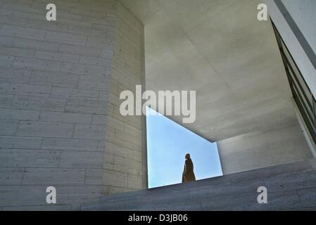 (dpa) - A woman enjoys the sun as she stands framed by the modern design in the entrance area of the Georg Schaefer - Stock Photo
