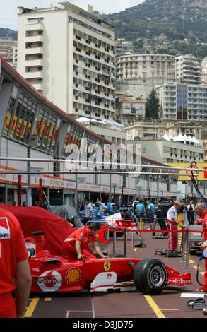 (dpa) - A mechanic of Ferrari racing team pushes a racing car out of the pits in front of  Monaco's skyline at the - Stock Photo