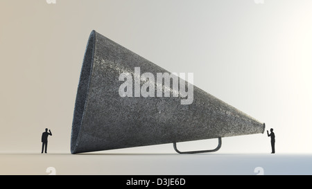 Tiny people communicating through a vintage megaphone - Stock Photo