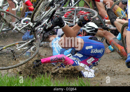 (dpa) - Italian cyclist Daniele Righi barges headfirst into dirty mud after a mass crash on cobblestone during the - Stock Photo