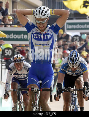 (dpa) - Belgian cyclist Tom Boonen (C) crosses the finish line and celebrates his triumph at the traditional Paris - Stock Photo