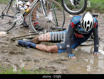 (dpa) - Spanish cyclist Allan Davis lies in dirty mud after a mass crash on cobblestonea during the traditional - Stock Photo