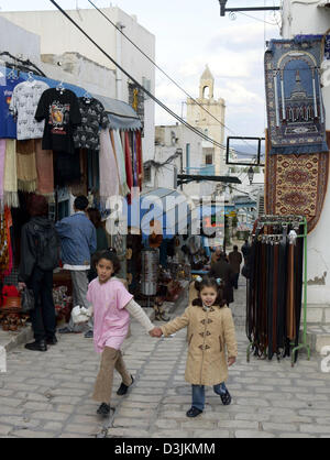 (dpa) - Two girls hold hands as they walk up a street with shops in the Medina oldtown in Sousse, Tunesia, 28 January - Stock Photo