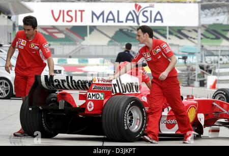 (dpa) - Ferrari mechanics push back the racing car of German Formula One driver Michael Schumacher into the pits - Stock Photo