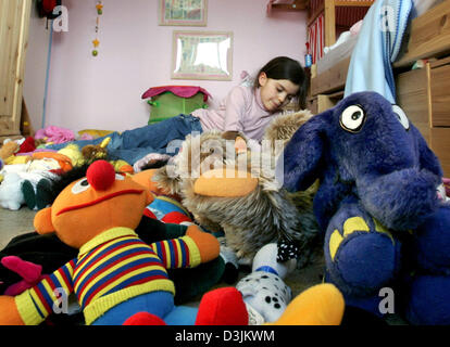 (dpa) - Seven-year-old Hanna plays while lying midst countless stuffed animals in Vluyn, Germany, 12 March 2005. - Stock Photo