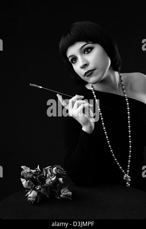 black and white: vintage styled portrait of a young beautiful woman with cigarette holder - Stock Photo