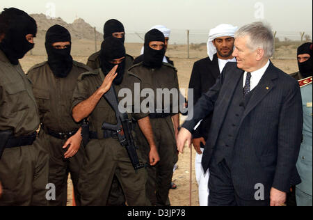 (dpa) - German Interior Minister Otto Schily (R) greets Iraqi policemen who have their faces hidden under ski masks - Stock Photo
