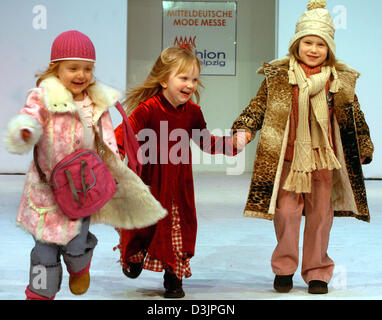 (dpa) - Children models (from L) Belinda, Vivien and Marie hold hands and smile as they walk down the catwalk presenting - Stock Photo
