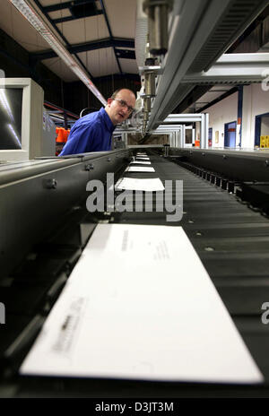 (dpa) - An employee of private German postal service MaxiMail observes a machine that automatically sorts letters - Stock Photo