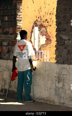 A victim of a landmine on crutches stands in a house in front of a grenade hole in the completely destroyed city - Stock Photo