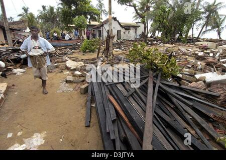 (dpa) - A man walks through debris and rubble in the destroyed city of Wadduwa, Sri Lanka, 28 December 2004. The - Stock Photo