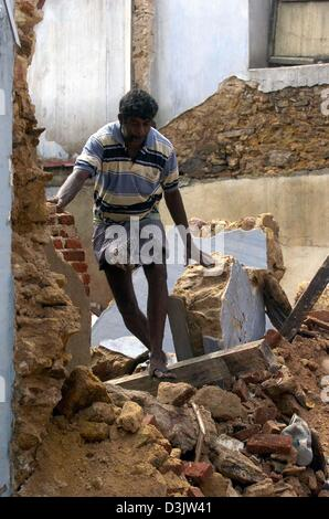 (dpa) - A man walks through debris and rubble in the destroyed city of Galle, Sri Lanka, 2 January 2005. The coast - Stock Photo