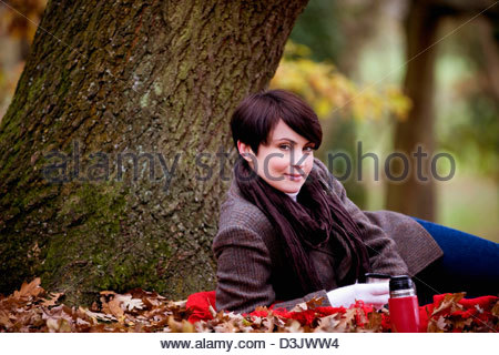A woman sitting under a tree holding a hot drink in autumn - Stock Photo