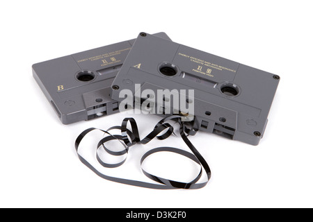 Obsolete magnetic audio cassette tapes partially unwound on a white background. - Stock Photo