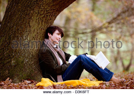 A woman sitting under a tree in autumn time, holding a book - Stock Photo